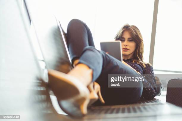 Young woman waiting for her flight using digital tablet