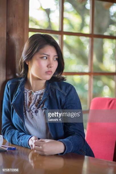 カフェで誰かを待っている若い女性