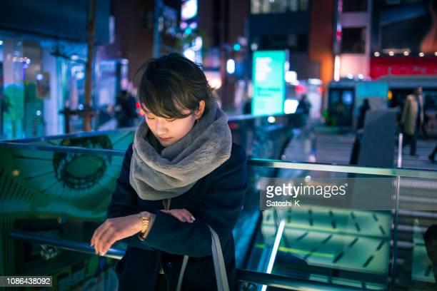都会の夜に誰かを待っている若い女性 - 待つ ストックフォトと画像