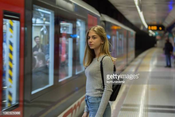 young woman waiting for the subway train - moving past stock pictures, royalty-free photos & images