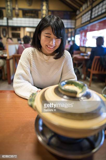Young woman waiting for tofu in hot pot