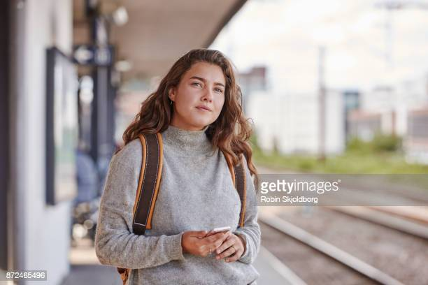 Young Woman waiting for train at station