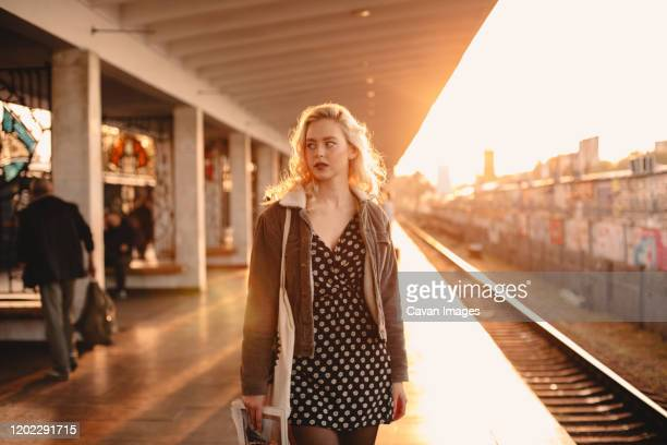 young woman waiting for train at subway station at sunset - 地下鉄のプラットホーム ストックフォトと画像