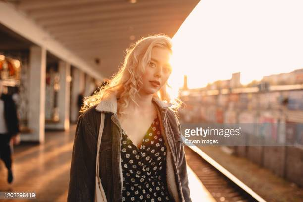 young woman waiting for train at subway station at sunset - golden hour stock pictures, royalty-free photos & images