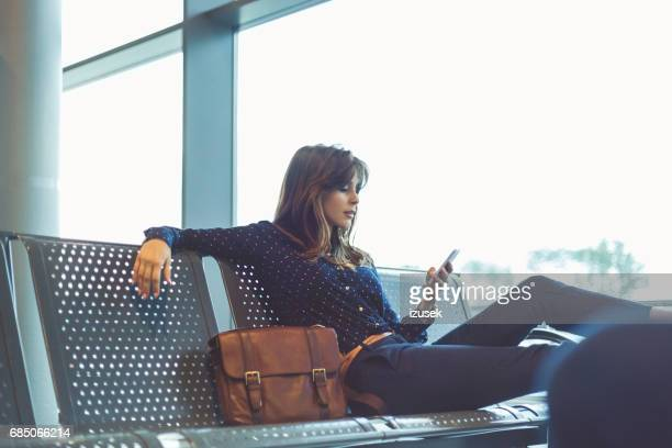 young woman waiting her flight at airport lounge - waiting stock pictures, royalty-free photos & images