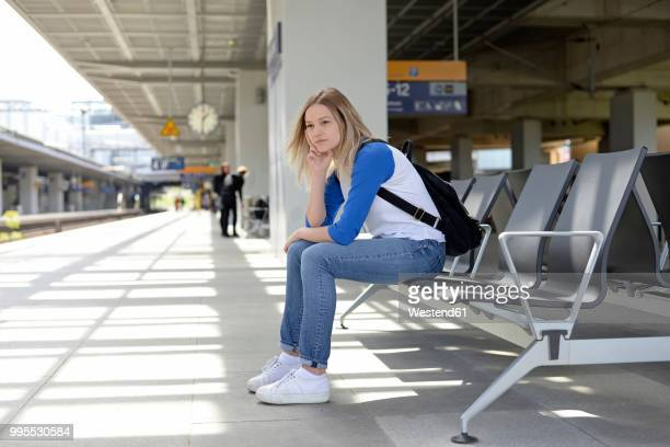 young woman waiting on bench of a platform in berlin - abwarten stock-fotos und bilder