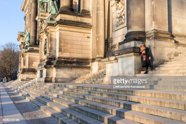 berlin, germany - december 21, 2016. young woman waiting on the steps of berlin's famous landmark, the berlin cathedral at sunset. berlin, germany. long shadows cover the steps of the church. - istock photos et images de collection
