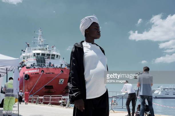 A young woman waits for first aid after have been landed in Naples from Vos Prudence a rescue boat of Msf About 1500 african refugees land in Naples...