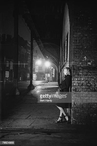 A young woman waits on a street corner in Elephant and Castle London 8th January 1949 Original Publication Picture Post 4694 Life In The Elephant pub...