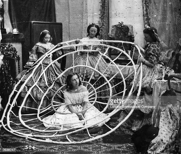 A young woman waits patiently whilst the hoops to support her crinoline are prepared London Stereoscopic Company Comic Series 504