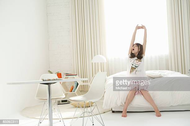 A young woman wakes up on bed in morning