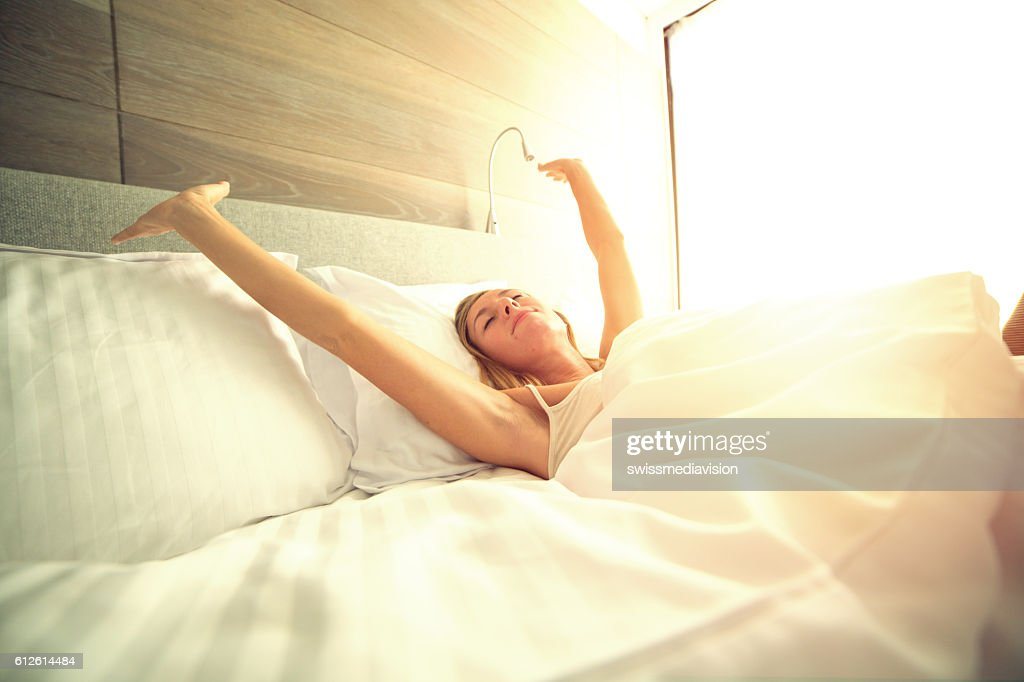 Young woman waking up in her hotel room, stretching arms : Stock Photo