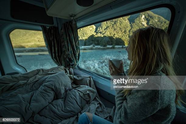 Young woman waking up in motor home
