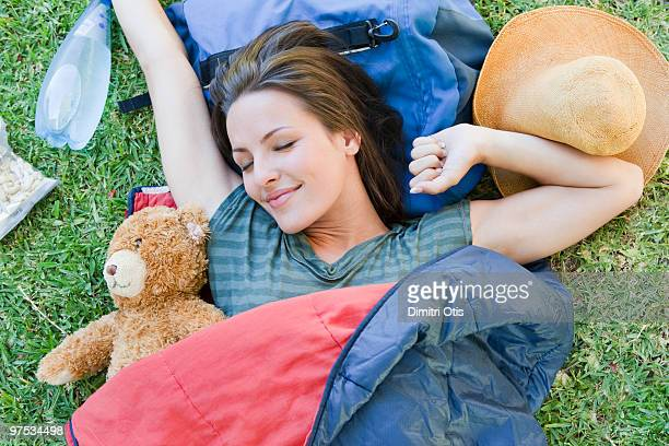 Young woman waking up outdoors with teddy bear