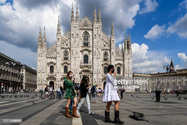 Young woman walk across Piazza del Duomo and the cathedral on June 3, 2020 in downtown Milan, as the country eases its lockdown aimed at curbing the...