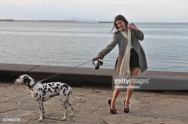 Young woman walking a dog by the water