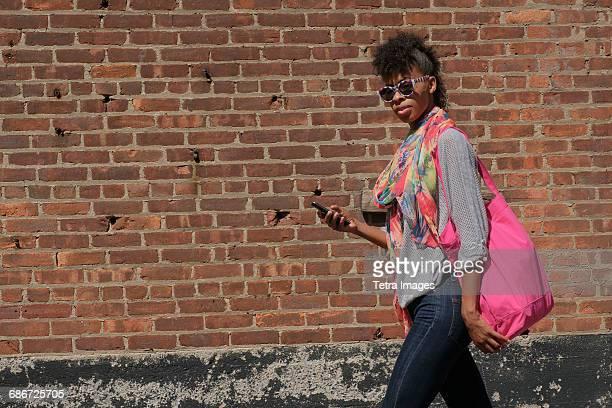 Young woman walking against brick wall