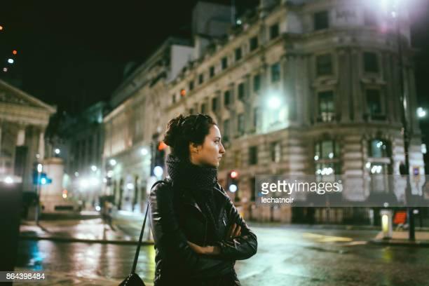 Junge Frau, die allein auf den Straßen von London in der Nacht zu Fuß