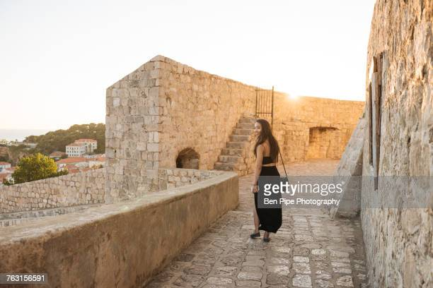 young woman walking along city walls, dubrovnik, croatia - long dress stock pictures, royalty-free photos & images