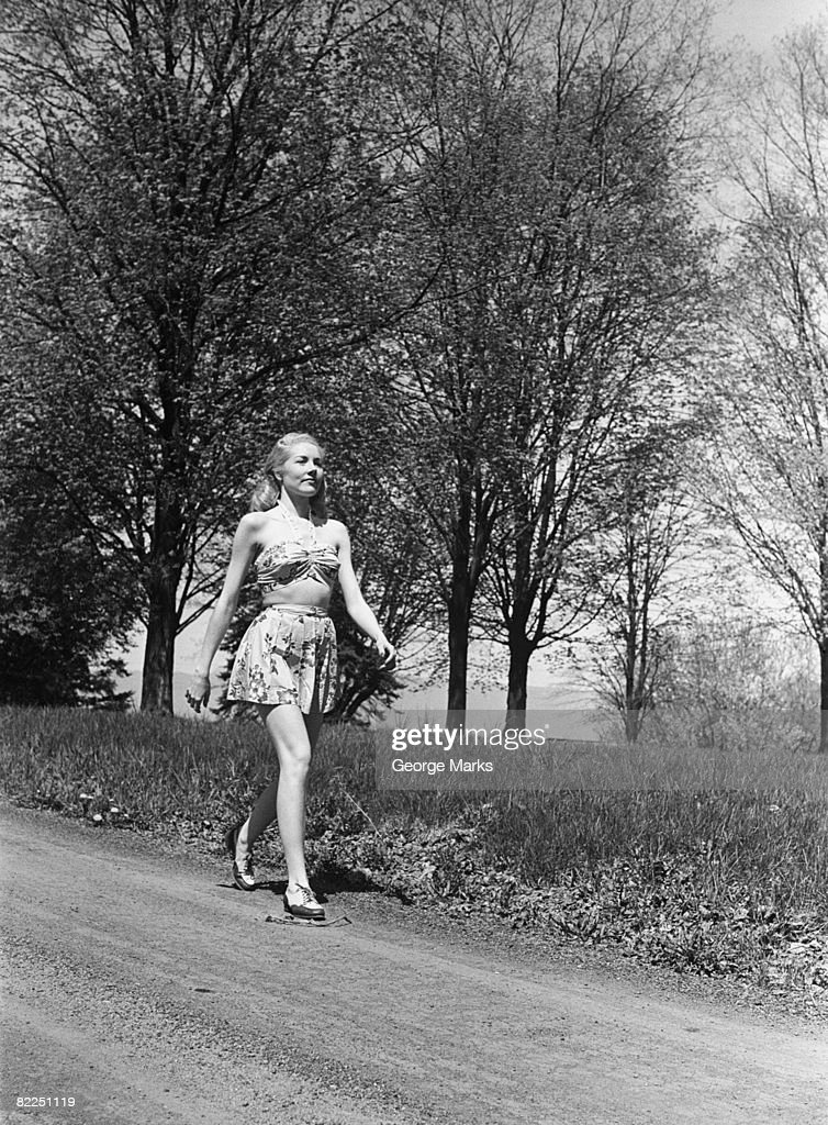 Young woman walking along country road : Stock Photo