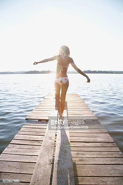 Young woman walking along dock