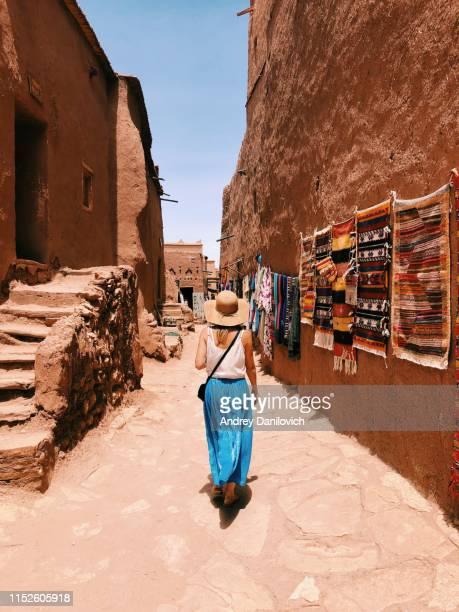 jovencita caminando por estrechas calles de la aldea de ait ben haddou en marruecos - marruecos fotografías e imágenes de stock