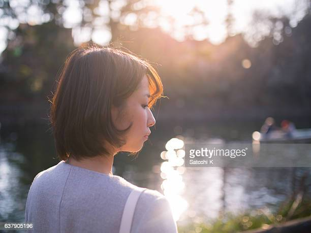 Young woman walking along pond in the evening