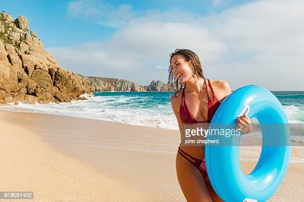 young woman walking along porthcurno beach on a bright day. - porthcurno stock pictures, royalty-free photos & images