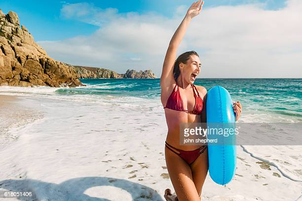 young woman walking along porthcurno beach on a bright day. - red tube stock photos and pictures