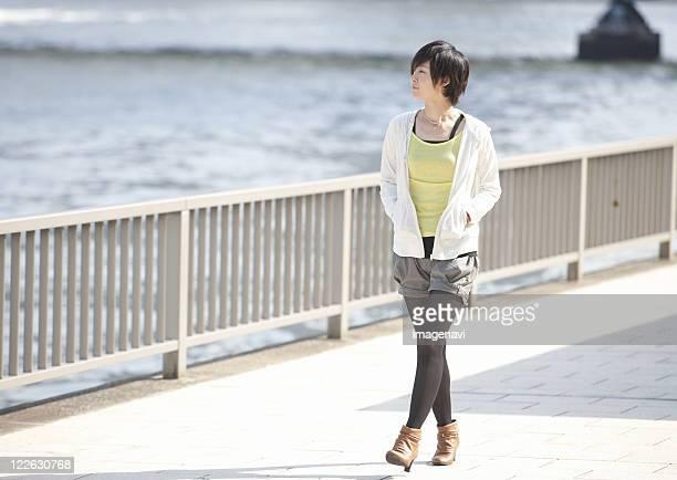 Young woman walking along river