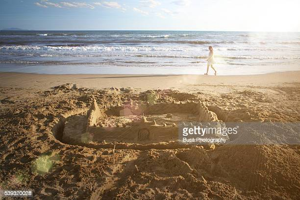 Young woman walking along the beach with a sande castle in the foreground
