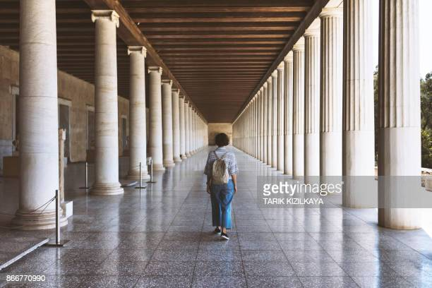 young woman walking along the hall with classic grek columns - athens greece stock pictures, royalty-free photos & images