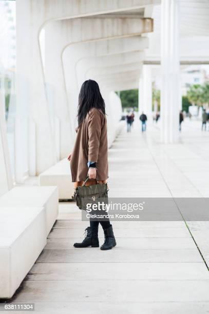 Young woman walking along the modern structure of the shoreline of Palmeral de las sorpresas (Malaga port) in Malaga, Andalusia, Spain