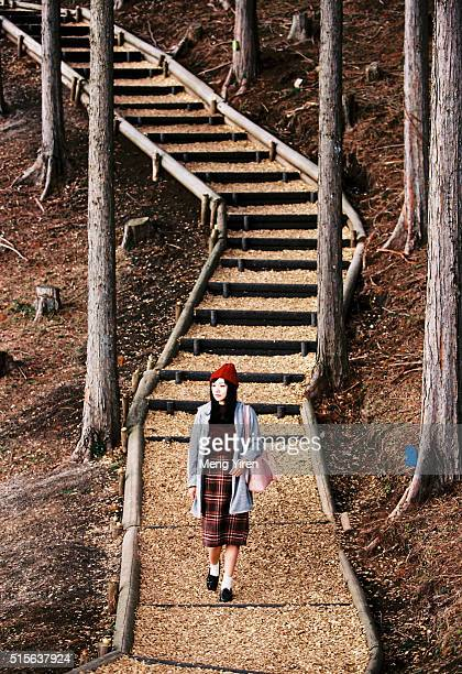 a young woman walking along the narrow path - mishima city stock photos and pictures