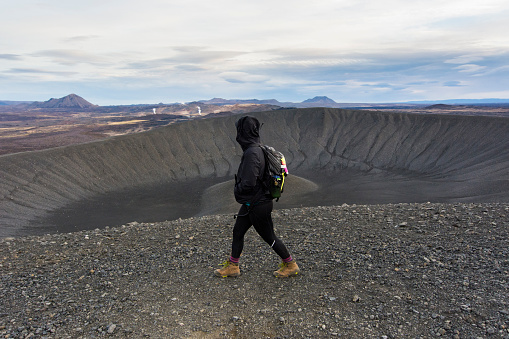 Young woman walking along the ridge of the Hverfjall crater with looking at the volcanic landscape in the background in the background. - gettyimageskorea