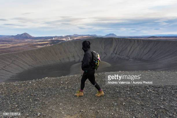 young woman walking along the ridge of the hverfjall crater with looking at the volcanic landscape in the background in the background. - volcanic crater stock pictures, royalty-free photos & images
