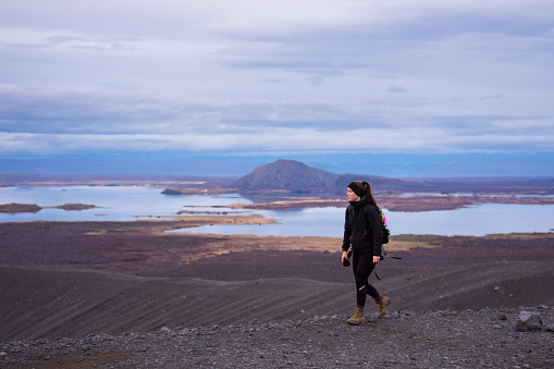 Young woman walking along the ridge of the Hverfjall crater with Lake Myvatn in the background. - gettyimageskorea
