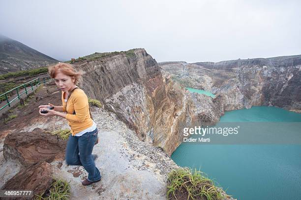 Young woman walking along the rim of Kelimutu volcano in Flores Indonesia