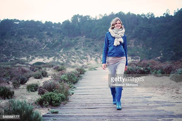 young woman walking along the wooden path - gummistiefel frau stock-fotos und bilder