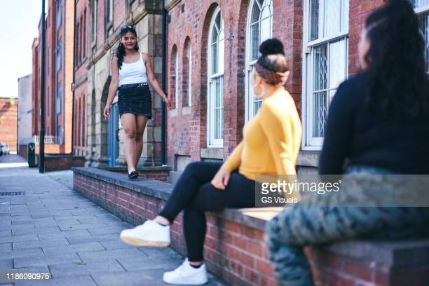 young woman walking along wall watched by teenage sisters - mini skirt stock pictures, royalty-free photos & images