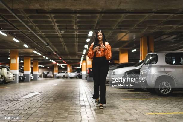 mujer joven caminando y usando el teléfono inteligente en el estacionamiento - aparcar fotografías e imágenes de stock