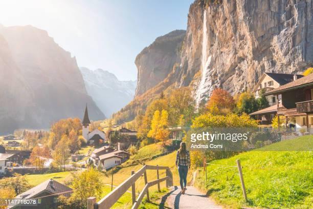 a young woman walking at lauterbrunnen village - lauterbrunnen - fotografias e filmes do acervo