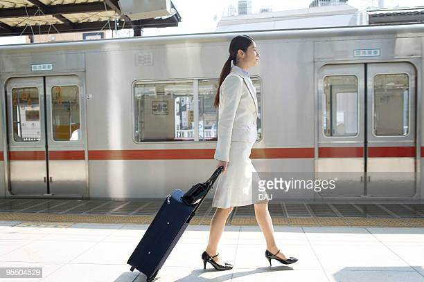 Young woman walking at platform, carrying suitcase