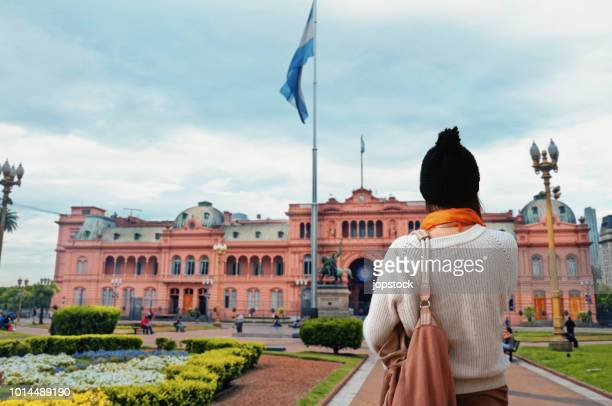 young woman walking at plaza de mayo square in buenos aires, argentina - buenos aires stock pictures, royalty-free photos & images