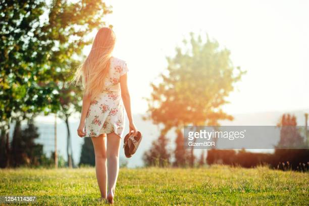 young woman walking at sunset - yellow dress stock pictures, royalty-free photos & images