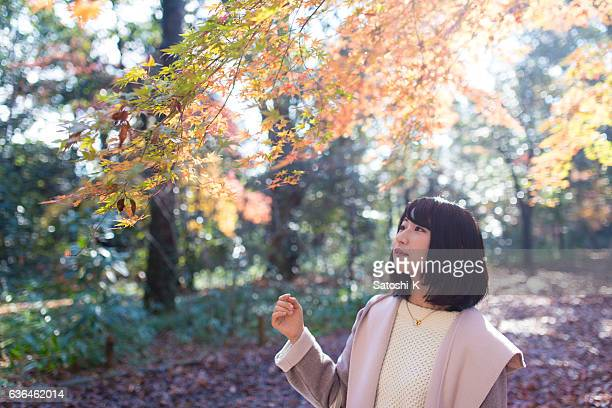 Young woman walking autumn forest in the morning