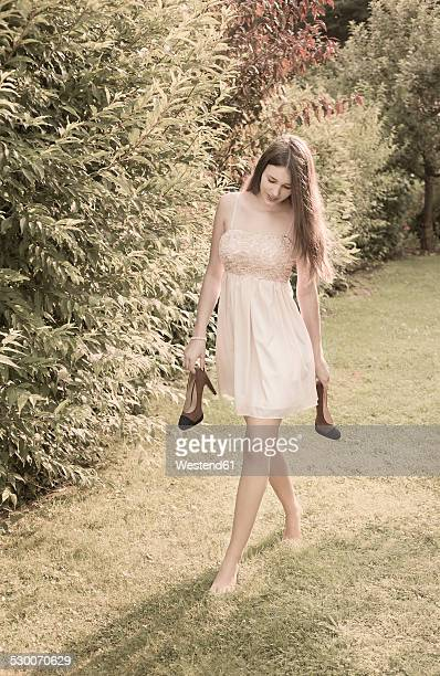 young woman walking barefoot on meadow in the garden - ragazzine scalze foto e immagini stock