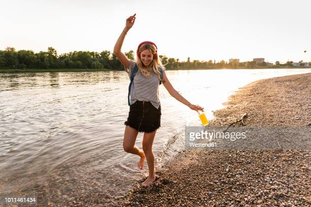 young woman walking barefoot on riverside, earphones and smartphone - freizeit stock-fotos und bilder