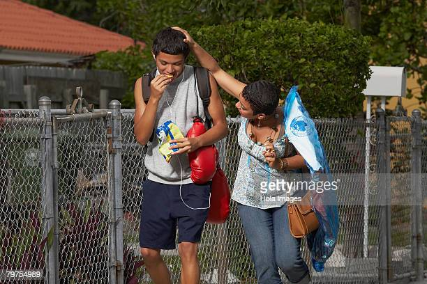 Young woman walking beside his brother and touching his head