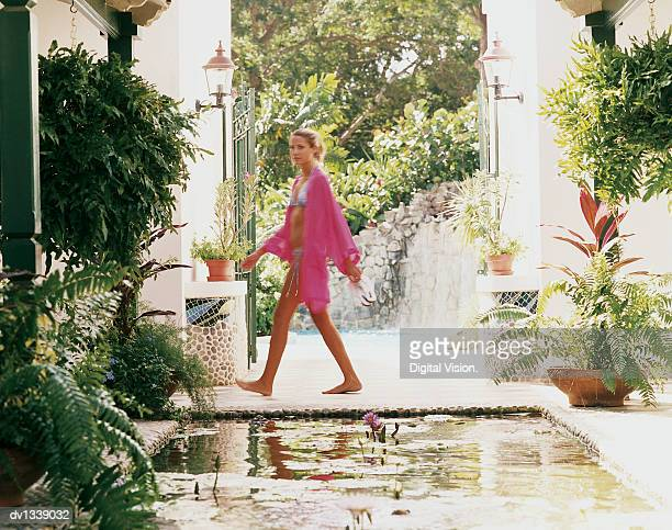 Young Woman Walking by a Pond in a Courtyard